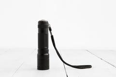 Pocket flashlight on white wooden background stock image