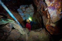 Pocket Gold Miner exiting from tight shaft. A pocket gold miner exiting a deep and tight shaft inside a tunnel dug for exploration of gold in Acupan Mines Stock Images