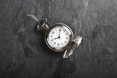 Pocket gray clock on dark gray. Slate texture Royalty Free Stock Photos