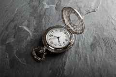 Pocket gray clock on dark gray. Slate texture Stock Photography