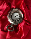 Pocket gray clock on red. Silk texture Royalty Free Stock Photography