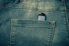 The pocket of jeans with lighter. Cloth background. Toned Royalty Free Stock Image