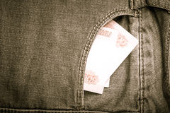 The pocket of jeans with money. Cloth background. Toned Stock Photo