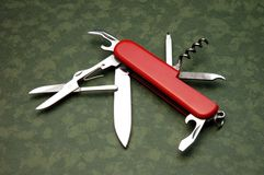 Pocket knife. On green camouflage background from above Stock Image