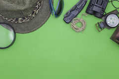 Pocket knife with compass,hat,glasses,rope,magnifying glass on g Royalty Free Stock Photography