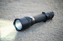 Pocket LED flashlight lies on a sand Royalty Free Stock Images
