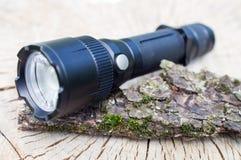 Pocket LED flashlight lies on a tree bark Stock Images