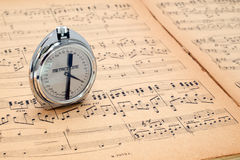 Pocket metronome  on an ancient music score Stock Images