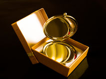 Pocket mirror and yellow box. On a black background Royalty Free Stock Photos