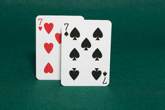 Pocket sevens. Closeup of pocket sevens starting hands in hold'em poker also called walking sticks in horizonal view royalty free stock image