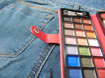 Pocket travel makeup palette on jeans. Small makeup palette in travel format laying on jeans Royalty Free Stock Photos