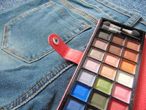 Pocket travel makeup palette on jeans. Small makeup palette in travel format laying on jeans stock photography