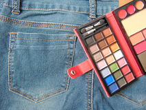 Pocket travel makeup palette on jeans. Small makeup palette in travel format laying on jeans royalty free stock images