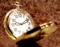 Pocket watch. Golden pocket watch over grunge background Stock Photography