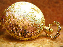 Pocket watch. Golden decorated pocket watch back over pink marble Royalty Free Stock Photos