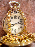 Pocket watch. Golden pocket watch over pink marble background Royalty Free Stock Photos