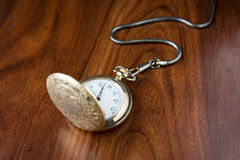 Pocket watch. Old pocket watch on dark brown table Royalty Free Stock Images