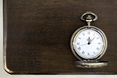 Pocket watch. Antique pocket watch on a wooden table Stock Image