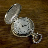 Pocket watch. This is a close view of a engraved handmade silver pocket watch on a wooden table Royalty Free Stock Photos
