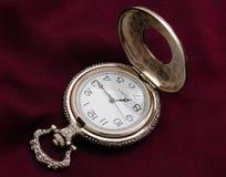 Pocket watch. Open silver pocket watch on purple silk background Royalty Free Stock Image