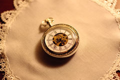 Old pocket watch on lace. An old pocket watch on a lace cloth Stock Image