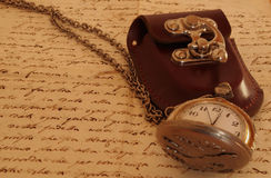 Pocket watch on an ancient manuscript Stock Photo