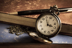 Pocket watch with antique book and pen. Royalty Free Stock Images