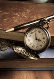 Pocket watch with antique book and pen Stock Photography