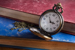 Pocket watch with antique book Royalty Free Stock Photos
