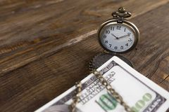 Pocket watch associated with cash in the tree. Time is money. Copy paste Stock Photography