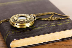 Pocket watch and book against a rustic background Royalty Free Stock Image