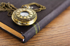 Pocket watch and book against a rustic background Royalty Free Stock Photography