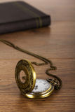 Pocket watch and book against a rustic background Stock Photography