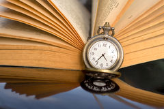 Pocket watch and book Stock Images