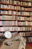 Pocket watch and bookshelf in the background Stock Photo