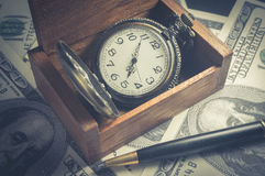 Pocket watch in box with pen and money. Royalty Free Stock Image