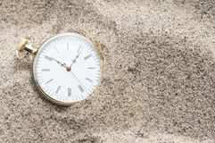 Pocket watch buried in sand Stock Images