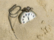 Pocket watch buried in sand. Royalty Free Stock Photography