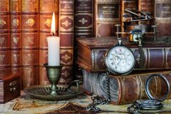 Pocket watch, burning candle and old books stock photo