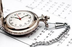 Of a pocket watch on a calendar Stock Images