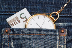 Pocket watch with chain in jeans and five euros. Royalty Free Stock Images