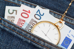 Pocket watch with chain in jeans and money euro. Royalty Free Stock Photo