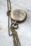Pocket watch with  chain on marble. Stock Photos