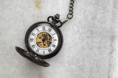 Pocket watch with  chain on marble. Royalty Free Stock Images