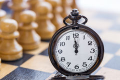 Pocket watch and chess pieces Royalty Free Stock Photo