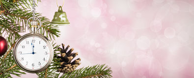 Pocket watch on Christmas tree branch on pink background Stock Photo
