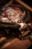 Pocket watch close-up lying on top of the package of Cuban cigar Royalty Free Stock Photo