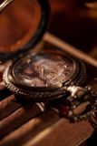 Pocket watch close-up lying on top of the package of Cuban cigar. Pocket watch on a chain lying on top of the package of Cuban cigars Stock Photo