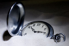 Pocket watch covered with sand. Antique pocket watch covered with sand (in the darkness Royalty Free Stock Photo