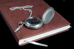 Pocket watch on diary page Stock Images